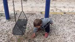 Toddler plays with stones from puddle 4 Stock Footage