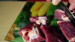 Closeup of the hands of a butcher cutting slices of raw meat off a large loin Stock Footage