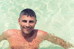 Happy man in 40s relaxing in tropical water - stock photo
