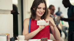 Young woman taking photo of food with cellphone sitting in cafe in the city HD Stock Footage