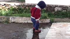 Toddler stands in puddle Stock Footage