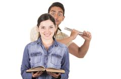 angry young man ready to throw book from behind towards naive sweet girl - stock photo