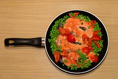Pan full of salmon steacks, peas, tomatoes and capers Stock Photos