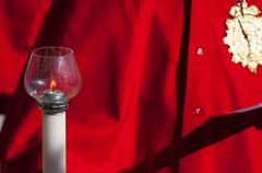particular of a candelabrum in front of a red coat - stock photo
