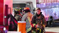Female fireman at the scene of an incident with colleagues Stock Footage
