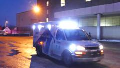 Ambulance escorted by police cruiser leaving with lights and sirens Stock Footage