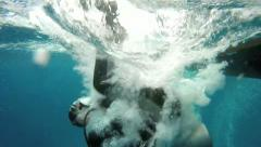 Scuba diver slow motion backwards roll entry off boat - stock footage
