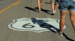 People walk over Route 66 sign during festival in Kingman, Arizona Stock Footage