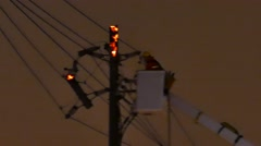 Fireman atop an elevated platform putting out a power pole fire Stock Footage