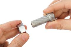 Stock Photo of Bolt and nut in hands isolated on white background