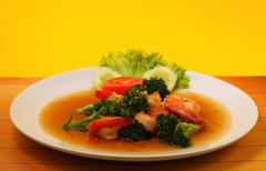 Shrimp and broccoli stir fry in sauce with a yellow background on a wood table - stock photo