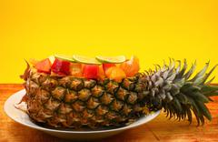 Thai style fruit salad inside a pineapple with a yellow background on a wood tab - stock photo