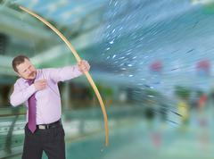Businessman practicing archery with modern interior in background Stock Photos