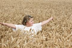 Little girl in the wheat Stock Photos