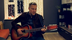 Man Plays Acoustic Guitar and Sings on Beautiful Background - stock footage