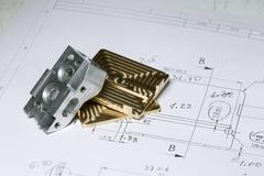 Stock Photo of Ready CNC golden and silver metal detail on technical drawing sketch with mea