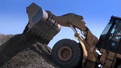 Tractor pours rubble from the ladle. - stock footage