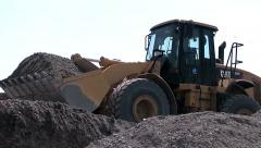 Tractor carries rubble in the ladle. - stock footage