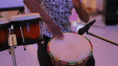 Young male percussionist playing cuban drums against black background Stock Footage