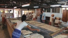 Women cook cassava biscuits at the Biscuiterie Rault in Mahebourg, Mauritius. Stock Footage