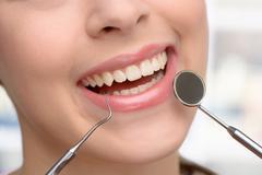Close up of beautiful woman visiting dentist - stock photo