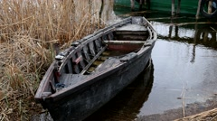 The old dilapidated single tarred fishing boat on the shore Stock Footage