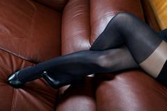 Female feet in black stockings on a leather sofa - stock photo