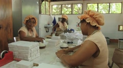 Women pack cassava biscuits at the Biscuiterie Rault in Mahebourg, Mauritius. Stock Footage