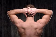 Close up of sporty man demonstrating back muscles - stock photo