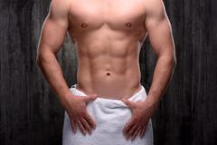 Close up of sporty man with towel on hips - stock photo