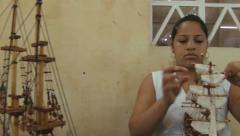 Woman fixes sails at the wooden ship model in a workshop in Curepipe, Mauritius. Stock Footage