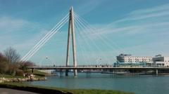 Suspension bridge train crossing blue sky clouds water Stock Footage