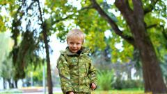 Portrait of cute 4 year old little child throwing autumn leaves at camera Stock Footage