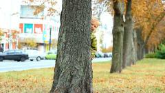 Cute boy hiding behind tree in park. playful kids Stock Footage