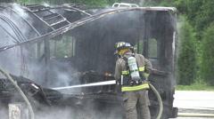 Fireman Spraying Water From Hose At Smoking Wreckage 01 Stock Footage