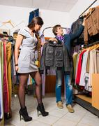 Shop assistant showing leather jacket to beautiful girl - stock photo
