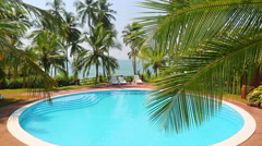 Palm leaf and swimming pool by the sea on a tropical resort Stock Footage