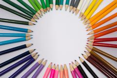Smiling sun arranged from crayons and pencil sharpenings. Stock Photos