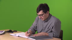 Mid Shot of a Man Writing at a Table Stock Footage
