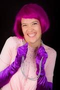 Woman dressed in shiny outfit and purple wig - stock photo