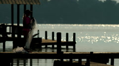 Girl fishing on a dock in the morning. Stock Footage