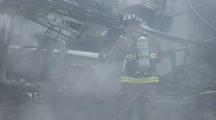 Fireman Spraying Water From Hose At Smoking Wreckage 02 Stock Footage
