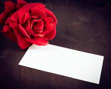 red rose and blank gift card for text on old wood background - stock photo