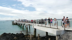 People walking from the ferry arriving at Rangitoto island Stock Footage