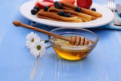 Honey dipper and pancakes on blue wooden Stock Photos