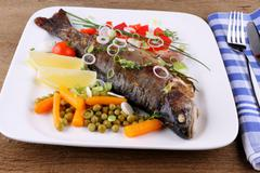 Grilled trout with quite different vegetables with cutlery - stock photo