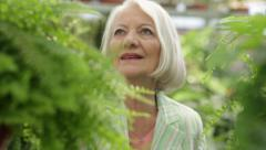 Elder woman looking plants in a flower shop - stock footage