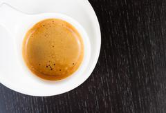 Detail of great italian coffee in a white cup on black wood table Stock Photos