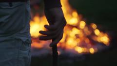 Young Man Throws Stick into a Bonfire Stock Footage