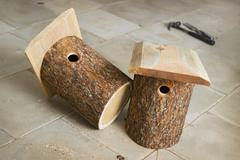 Two birdhouse of alder logs Stock Photos